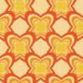 オレンジの花のようなモチーフが重なりあう少しレトロなパターン